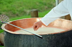 Cheesemaker checks with hand the milk's temperature inside the c Royalty Free Stock Photography
