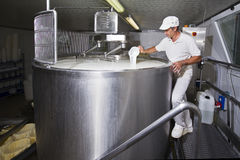 Cheesemaker pours rennet Stock Photo