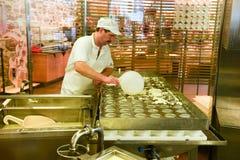 Cheesemaker som förbereder osten i ett showmejeri på Engelberg Arkivfoto