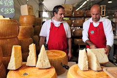 Cheesemakers and wheels of Parmesan in Italy. Stock Photo