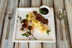 Cheeseplate con souce su una tavola immagine stock