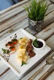 Cheeseplate mit souce auf einer Tabelle lizenzfreie stockbilder