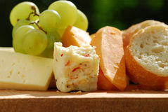 Cheeses. Assorted cheeses with grapes and white bread Royalty Free Stock Image
