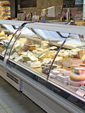 Cheeses from around the world. Photo of different cheeses being displayed in a chiller counter at an indoor market Royalty Free Stock Photo