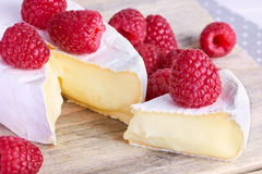 Cheeses on background with raspberry Royalty Free Stock Photos
