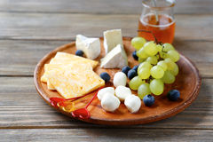 Cheeses with bunch of grapes Stock Photo