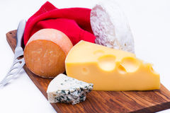 Cheeses on chopping board Stock Images