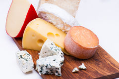Cheeses on chopping board Stock Image