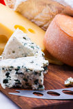 Cheeses on chopping board Stock Photo