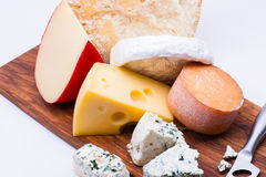 Cheeses on chopping board Royalty Free Stock Photo