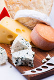 Cheeses on chopping board Royalty Free Stock Images