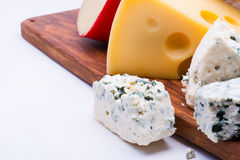 Cheeses on chopping board Stock Photos