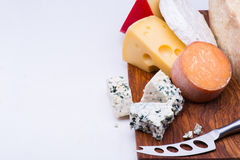 Cheeses on chopping board Royalty Free Stock Image