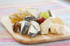 Cheeses. Delicatessen cheeses on a wooden platter Royalty Free Stock Photo