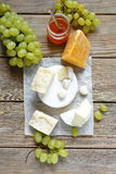 Cheeses and fresh grapes Stock Photos