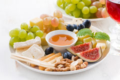 Cheeses and fruits, wine and snacks, closeup Stock Images