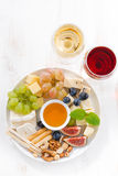Cheeses, fruits, wine and snacks on plate, vertical top view Stock Images