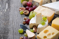 Cheeses, grapes and walnuts on a wooden background, horizontal Stock Photography