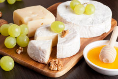 Cheeses, grapes and walnuts on a wooden background, horizontal Stock Image