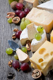 Cheeses, grapes and walnuts on a wooden background, top view Stock Photography