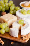 Cheeses, grapes and walnuts on a wooden background. Vertical, close-up Royalty Free Stock Images