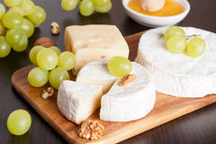 Cheeses, honey, grapes and walnuts on a wooden background. Cheeses, grapes and walnuts on a wooden background, horizontal, close-up Royalty Free Stock Photography