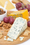 Cheeses with mold, grapes, crackers, jam and nuts on a board Royalty Free Stock Image