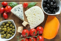 Cheeses and olives. Delicacy. Food composition - different types of cheeses, olives and tomatoes Stock Photos
