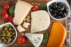 Cheeses and olives. Food composition - different types of cheeses, olives and tomatoes Royalty Free Stock Photo