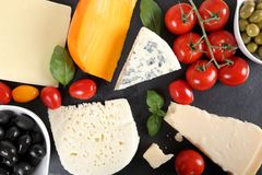 Cheeses and olives. Food composition - different types of cheeses, olives and tomatoes Stock Photos