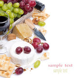 Cheeses, red and green grapes, crackers and wine, isolated Stock Photo