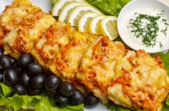 Cheesy bake. Cheesy baBaked fish fillet with cheese and tomatoes with vegetableske Stock Image