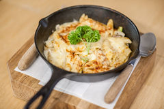 Cheesy baked macaroni. And cheese pasta portion with parmesan sprinkled on top - soft focus point Royalty Free Stock Image