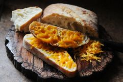 Cheesy garlic bread. Cheddar cheese garlic bread on wooden serving tray in kitchen Stock Photography