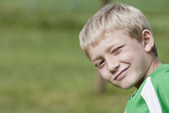 Cheesy grin. Young blonde boy with a cheeky wink stock images
