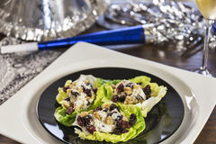 Cheesy lettuce boat appetizers are served at a New Years eve holiday party. Stock Photos