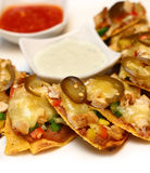 Cheesy nachos with sliced vegetable. Cheesy nachoes with sliced vegetable, chili and tartar sauce Stock Photo