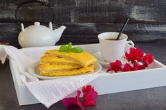 Cheesy pancakes with tea on a wooden tray. Stock Images