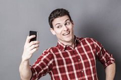 Cheesy young athletic man enjoying taking selfie for seduction Royalty Free Stock Images