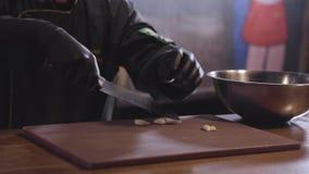 Chef écrasant avec l'ail aromatique de couteau pointu en métal sur le conseil en bois pour préparer la marinade dans le grand pla banque de vidéos
