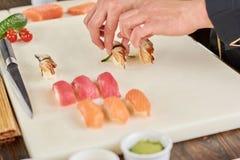 Chef übergibt das Setzen von Sushi mit Aal auf weißes Brett Stockfotografie