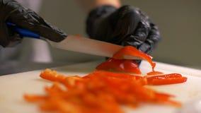 Chef übergibt den Schnitt des roten bulgarischen Pfeffers in Stücke für das Kochen des Gemüsesalats stockfotos