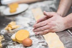 Chef& x27; руки s подготавливают итальянской заполненный едой равиоли макаронных изделий Стоковое фото RF