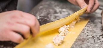 Chef& x27; руки s подготавливают итальянской заполненный едой равиоли макаронных изделий Стоковые Фотографии RF