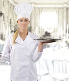 The chef. Blond and young woman in white chef dress with hat Royalty Free Stock Image