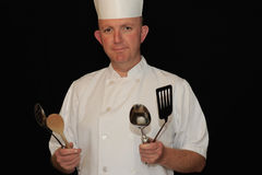 Chef. Man in chef uniform holding cooking utensils Stock Photography