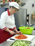 Chef. A female chef working in an industrial kitchen, standing at a table, cutting vegetables, focused on her work. Motion blurred knife Royalty Free Stock Image