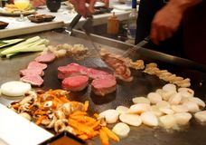 Chef in action. Scenes from a Tepanyaki style japanese cuisine performance in a restaurant Royalty Free Stock Image