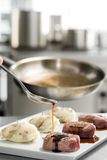 Chef add sause to a beef steaks, light one Royalty Free Stock Images