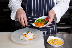 Chef add vegetables to risotto. In a plate Stock Image